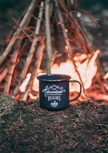 Black campers mug next to a fire in the wilderness