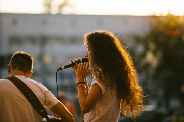 Young woman singing at an evening music festival at a live golden hour