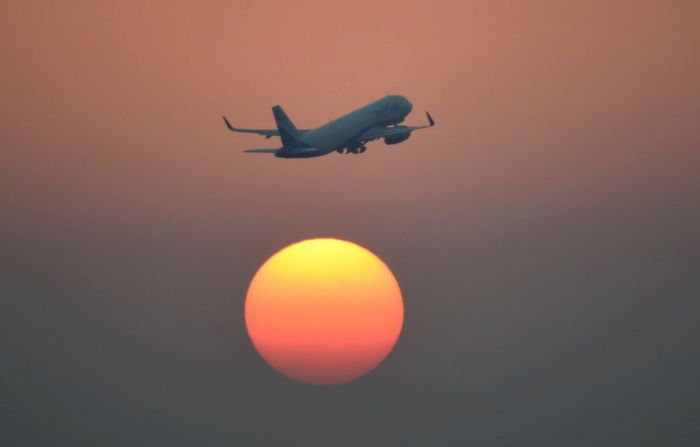 An airliner of India's IndiGo carrier flies over the setting sun in New Delhi on February 10, 2016