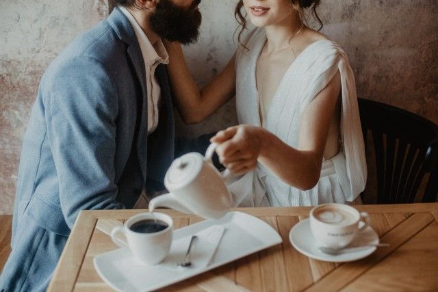 Couple drinking coffee during their wedding reception party