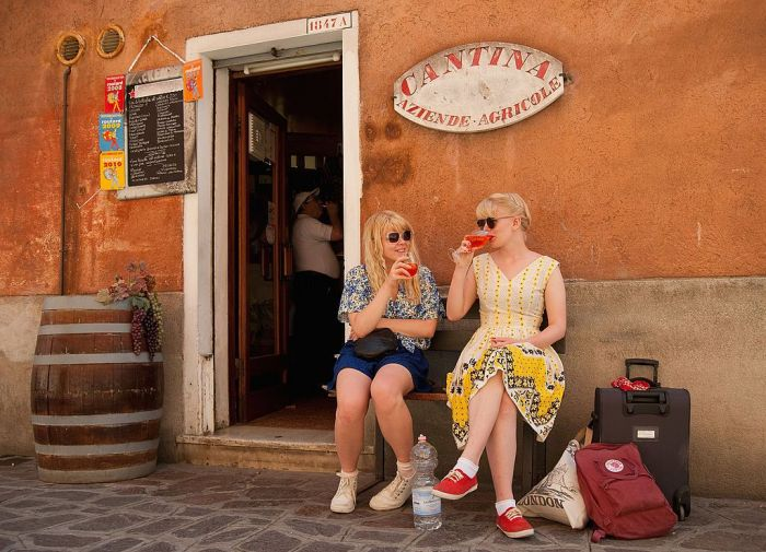 Two tourists enjoy a Spritz (a powerful mixture of white wine, Campari and soda water) in front of a traditiona bacaro on June 17, 2011 in Venice, Italy.