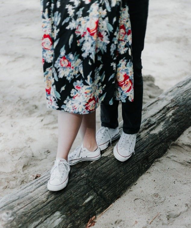 Man and woman walking along a fallen tree on the beach wearing white Converse sneakers