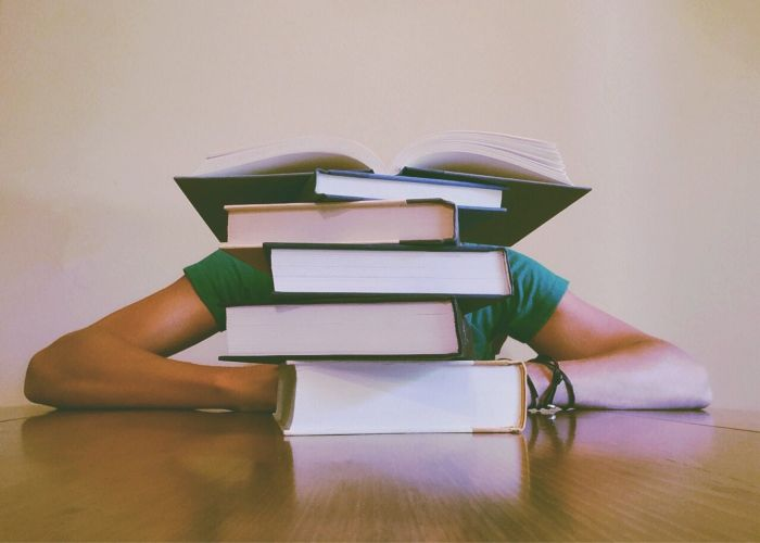 Student hiding behind a stack of books