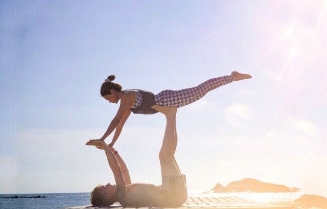 A couple doing high level of yoga posture supporting in each other with harmony on the beach in the sunny day.