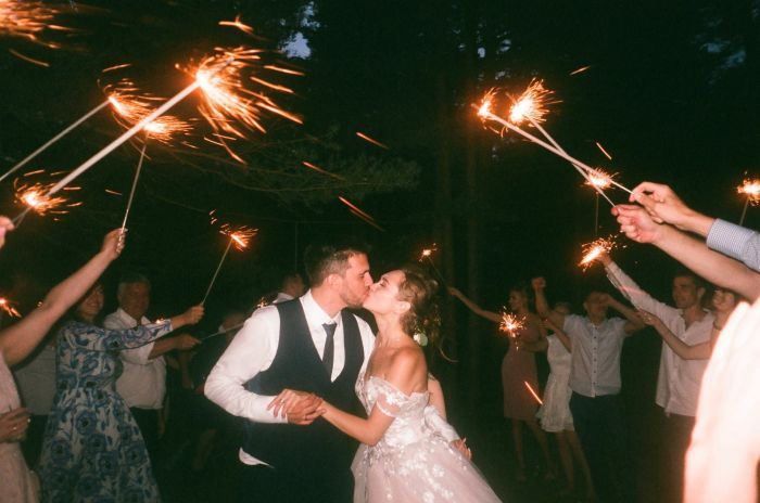 People raising lit sparkles while encircling bride and groom kissing