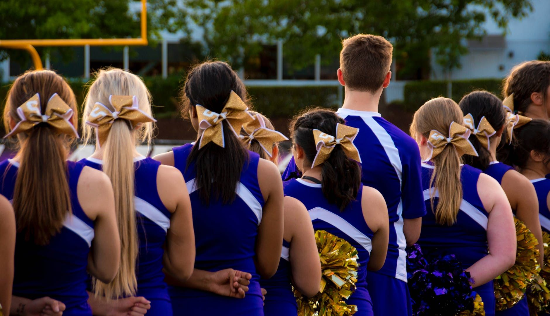 Cheerleaders wearing blue and white unfirom with gold bow and gold pompoms