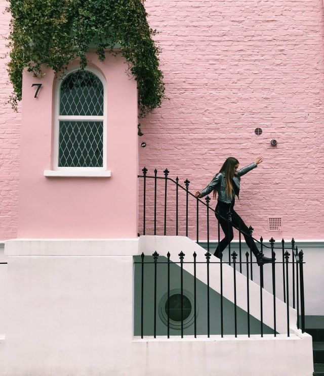 Meillennial woman wearing all black clothing skipping down the steps of an all pink building