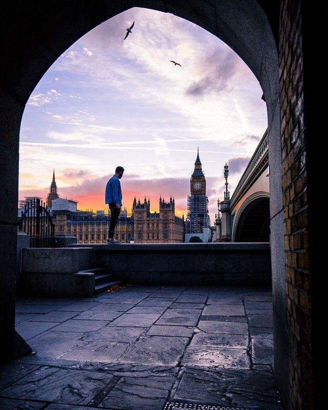Man in a jean jacket staring out at the sunset over the Big Ben clock tower in London