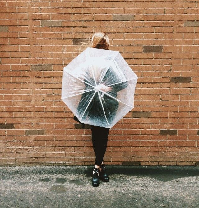 Blonde hair woman hiding her face behind a clear umbrella standing casually against a brick wall