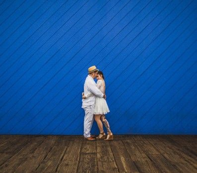 Bride and groom hugging in front of a bright blue wall and wooden floor