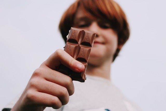 Red haired kid holding up a Cadbury chocolate bar