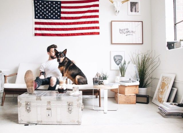 Man and dog lounge in white urban loft with an American flag and coffee
