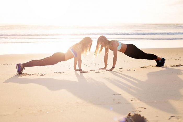 Two women planking at the seashore while the sun sets. Both women are wearing workout leggings and sports bras, sneakers and fitness watches with their hair down.