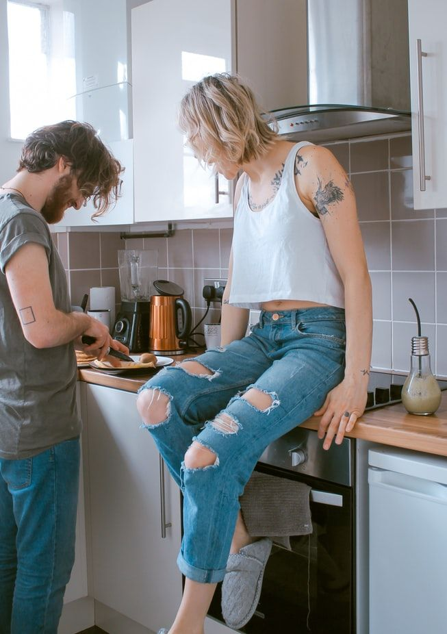 Hipster man in a green t-shirt and jeans is cutting food in his kitchen while a blonde haired woman in ripped jeans and a white tank top showing her tattoos watches him.