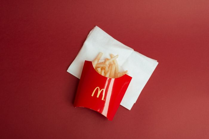 Red container from the fast food chain McDonald's with french fries and napkins.