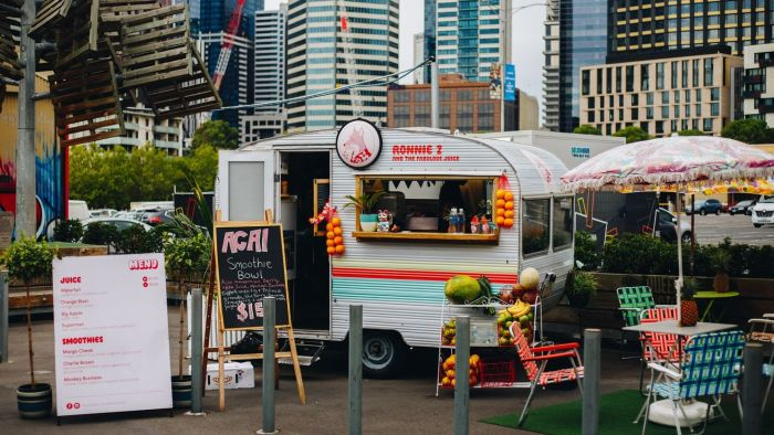 Outdoor fast food truck parked in city with seating and summer fruits and seating