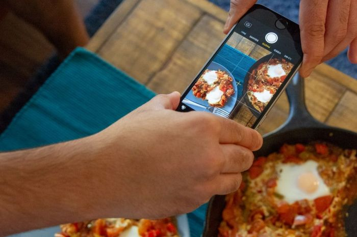 Man taking a picture of shakshuka he made in a skillet