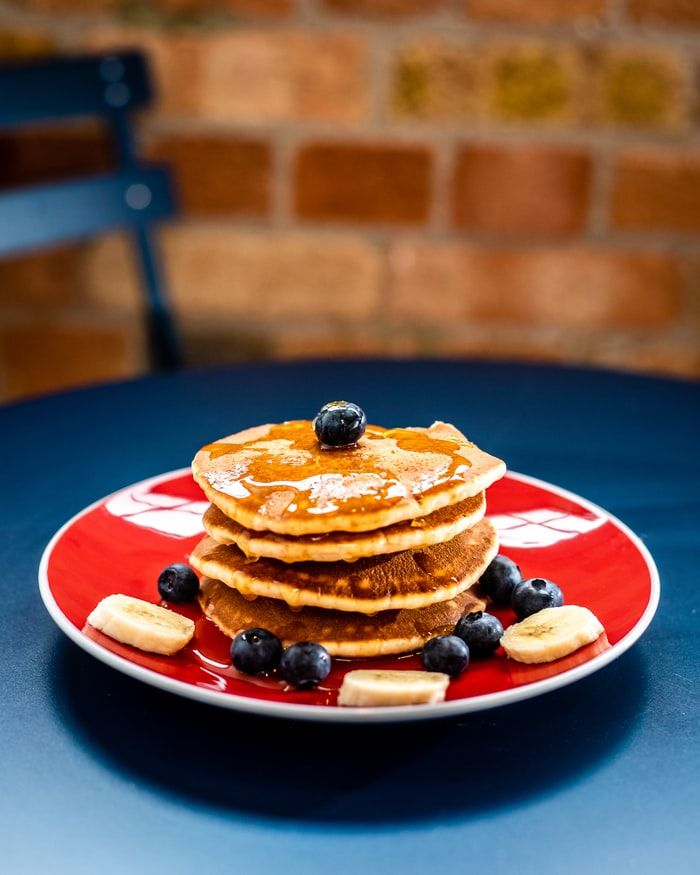 Stack of four pancakes on a red plate topped with banana slices and blueberries