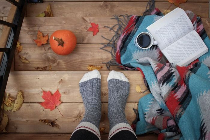 Person wearing grey sock standing on stairs with pumpkins and blankets and leaves