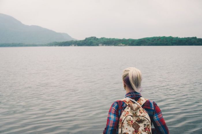 Blonde woman wearing a plaid shirt and backpack facing body of water