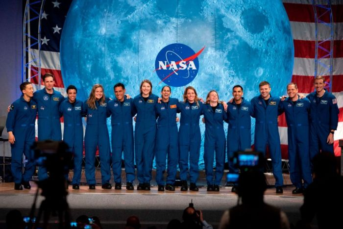NASA and Canadian Space Agency (CSA) astronauts acknowledge the audience after their graduation ceremony at Johnson Space Center