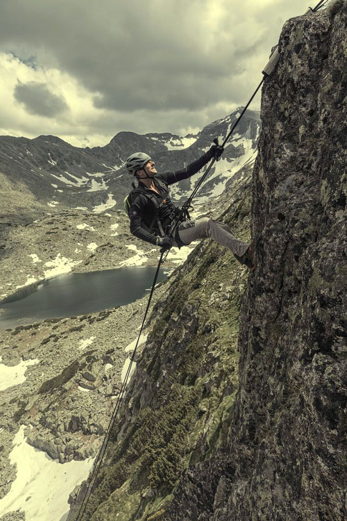 Bear Grylls climbing up a mountain wearing a helmet and a rope