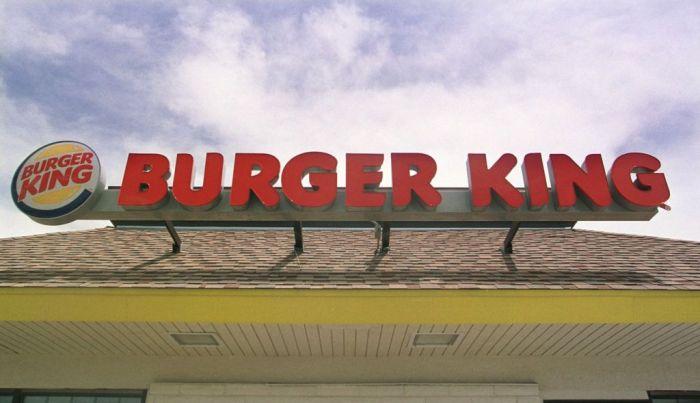 The Burger King logo and sign sit atop a Burger King restaurant