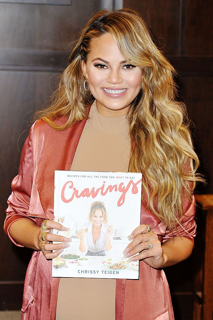 Chrissy Teigein holding her cookbook